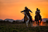 silhouette two cowboys ride with they horses under sunset