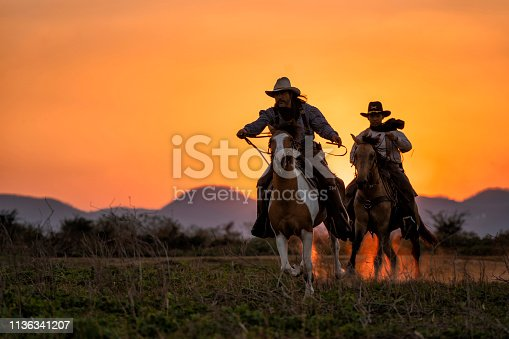 silhouette two cowboys ride with they horses under sunsetsilhouette two cowboys ride with they horses under sunset