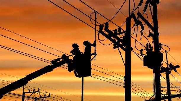 silhouet twee elektriciens met loskoppelen stok gereedschap op kraan truck werken aan elektrische transmissie te installeren op power pole - elektrische leiding stockfoto's en -beelden