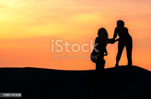 istock silhouette two woman giving hand help her friend hiking climbing to mountain peak at sunset. 1050742426