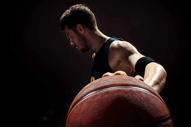 Silhouette view of a basketball player holding basket ball on - foto stock