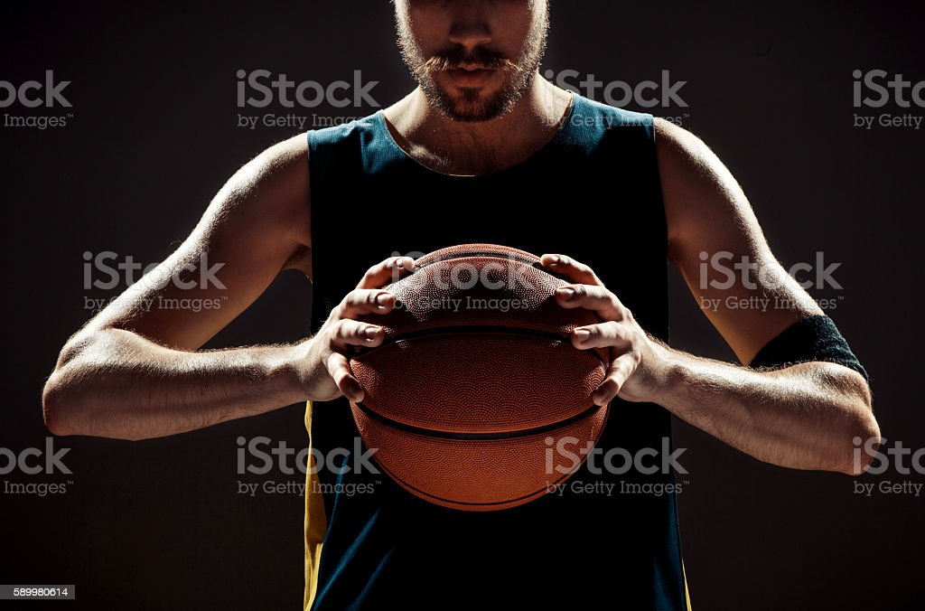 Silhouette view of a basketball player holding basket ball on stock photo