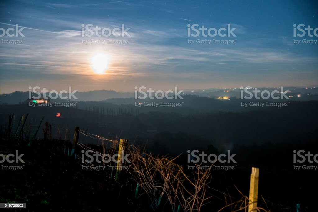 Silhouette vineyards on hills against sky stock photo
