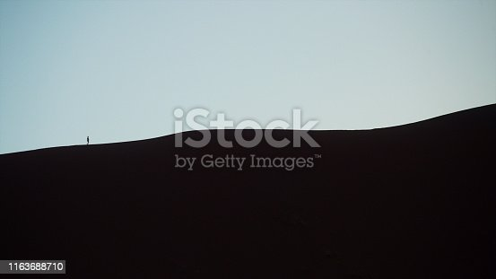 Boy climbing a sand dune at dusk seeing his silhouette as he walks further and higher on his journey to the summit in the Namibian Desert Namibia Africa