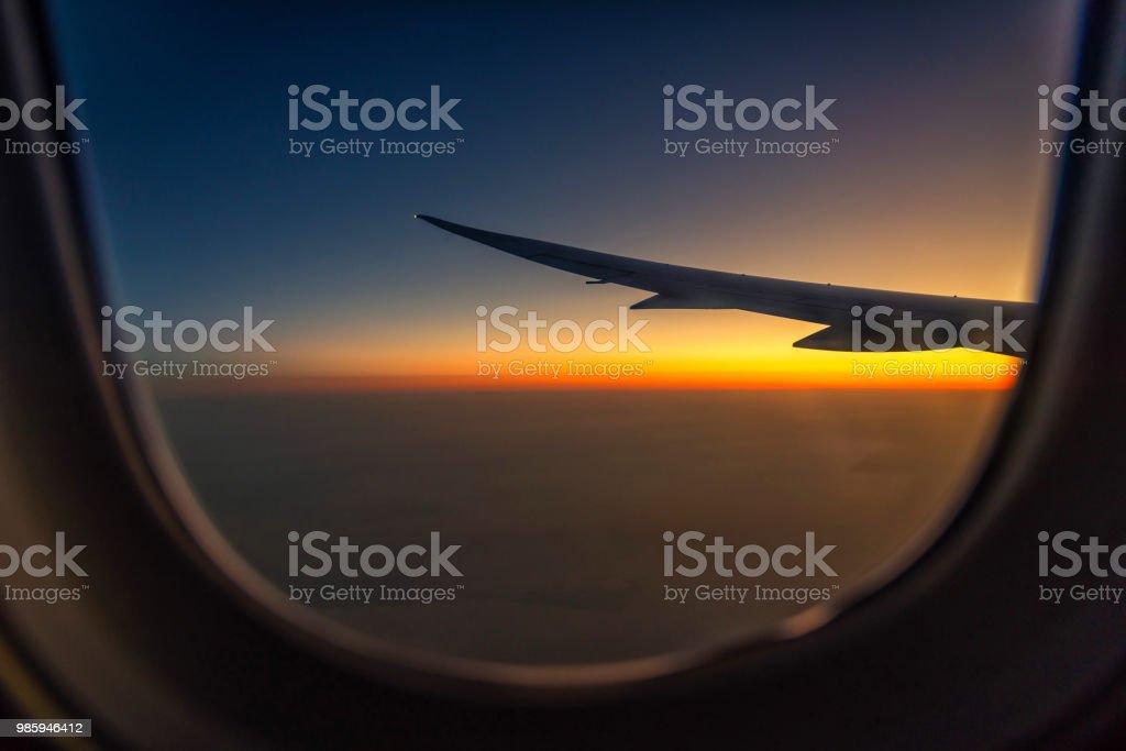 a49dedd6f7 Aile de silhouette d'un avion au lever du soleil vue par la fenêtre.