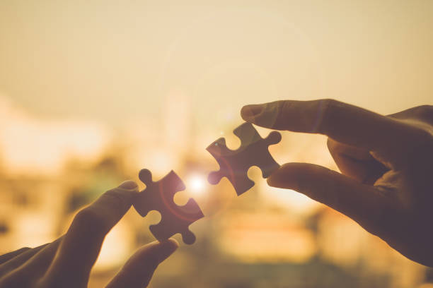 silhouette woman hands connecting couple puzzle piece against sunrise effect, businesswoman holding jigsaw with sunset background. business solutions, target, success, goals and strategy concepts - puzzle foto e immagini stock