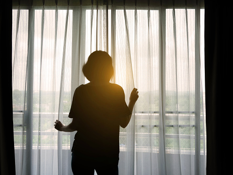 istock Silhouette woman opening curtain in the bedroom after getting up in the morning 1010428280