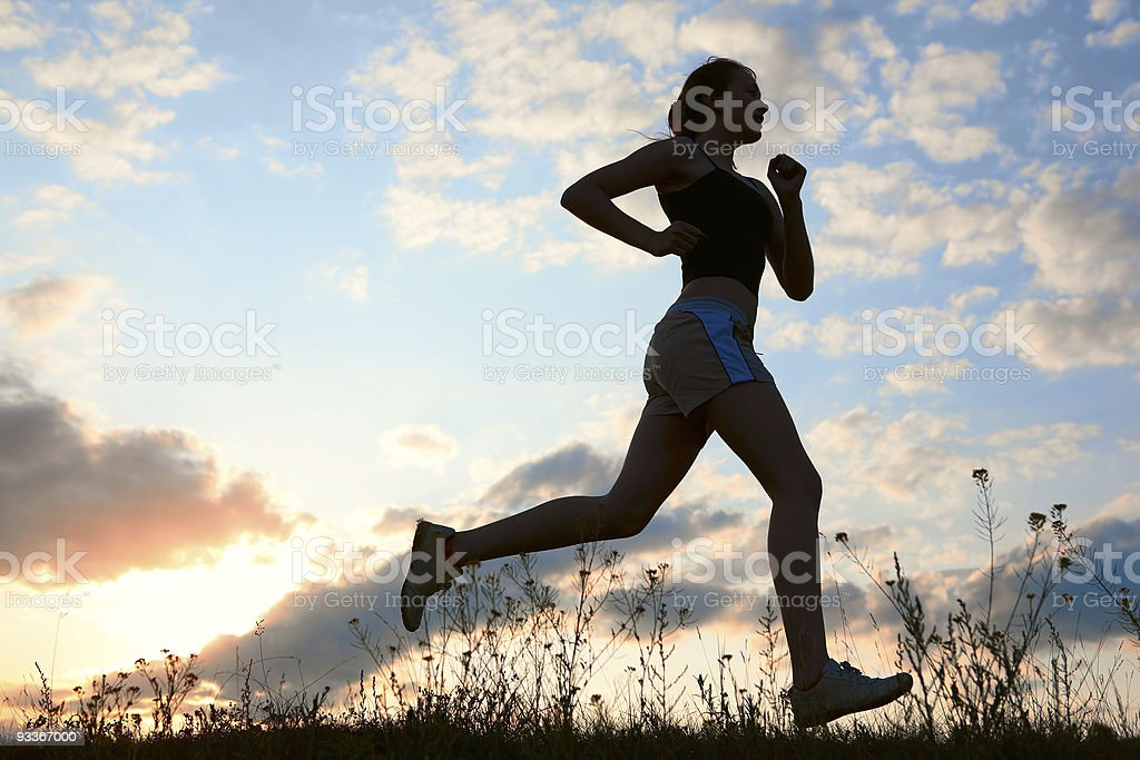 Silhouette woman run under blue sky with clouds stock photo