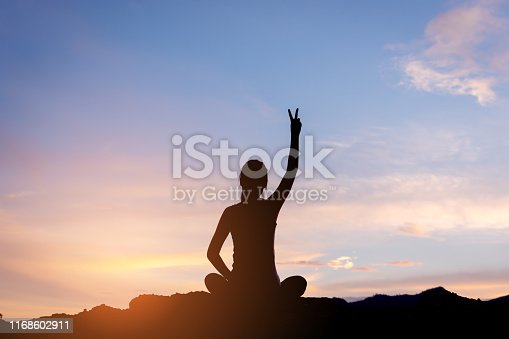 istock silhouette woman sitting and fighting  movitation feeling on top of mountain 1168602911