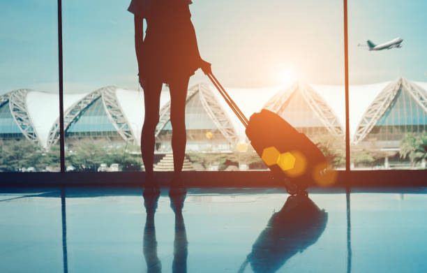 Silhouette woman travel with luggage looking without window at airport terminal international or girl teenager traveling in vacation summer relaxation holding suitcase and backpack stock photo