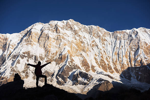 Silhouette women backpacker on the rock and Annapurna I Background stock photo