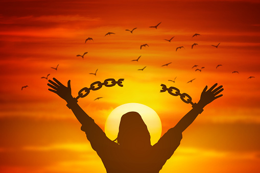 silhouette women hand up and broken chain and bird sunrise background .freedom concept