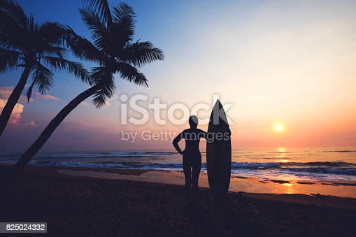Silhouette women surfer on tropical beach at sunset. landscape of summer beach and palm tree at sunset. vintage color tone