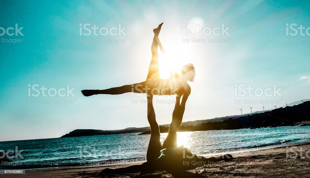 Silhouette young couple doing acro yoga outdoor on the beach - Woman and man training on evening time at sunset - Concept of fitness exercise for healthy lifestyle - Focus on bodies stock photo
