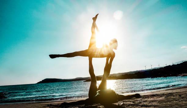 Couple jeune silhouette faire acro yoga en plein air sur la plage - femme et homme, formation sur temps au coucher du soleil du soir - Concept d'exercice de remise en forme pour le mode de vie sain - mettre l'accent sur le corps - Photo