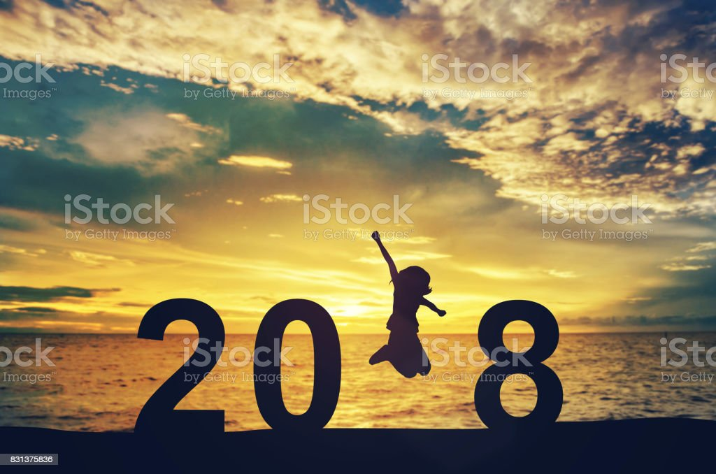 Silhouette young woman jumping on the sea and 2018 years while celebrating new year stock photo