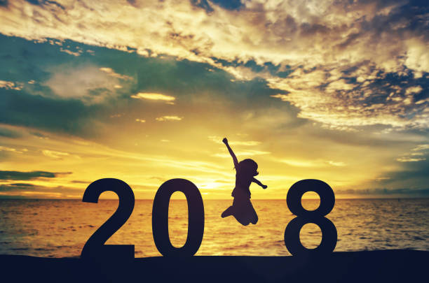 silhouette young woman jumping on the sea and 2018 years while celebrating new year - new year day stock photos and pictures