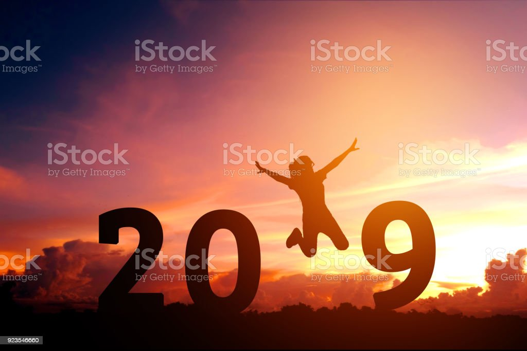 Silhouette young woman jumping to 2019 new year stock photo