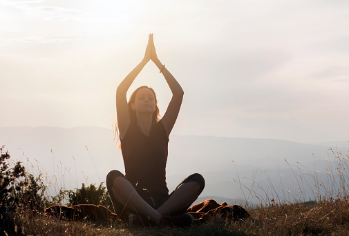 Silhouette young woman practicing yoga lotus position, meditating on mountain peak