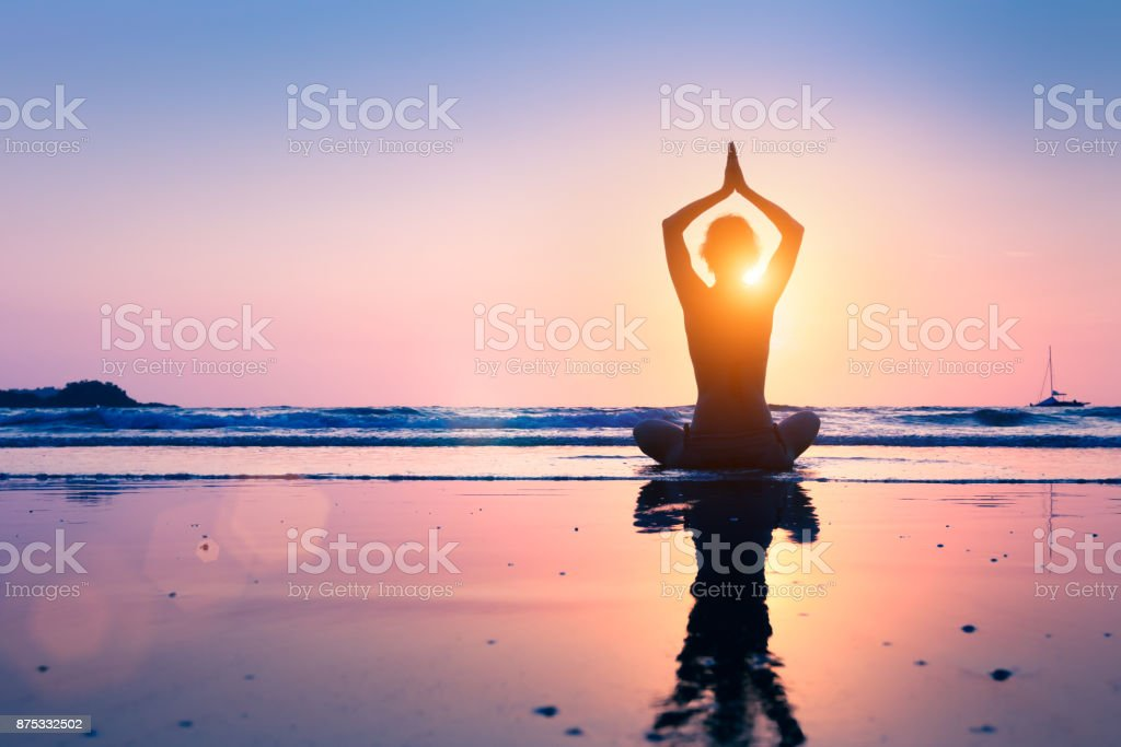 Silhouette young woman practicing yoga lotus position, meditating, beach - fotografia de stock