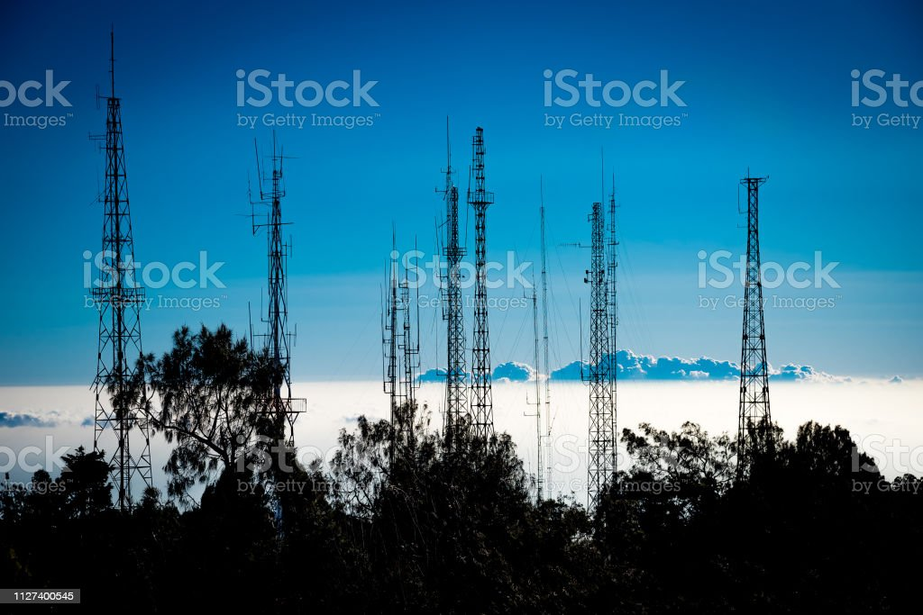 Some silhouetted antennas on the top of a hill with blue sky.