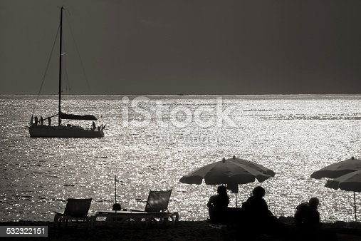 Vintage style black and white image with silhouetted beach figures at dusk, deck chairs, sun umbrellas, unrecognizable human figures sitting on the sand and sailing boat mooring in front of Los Cristianos beach, Southern Tenerife, Canary islands, Spain..