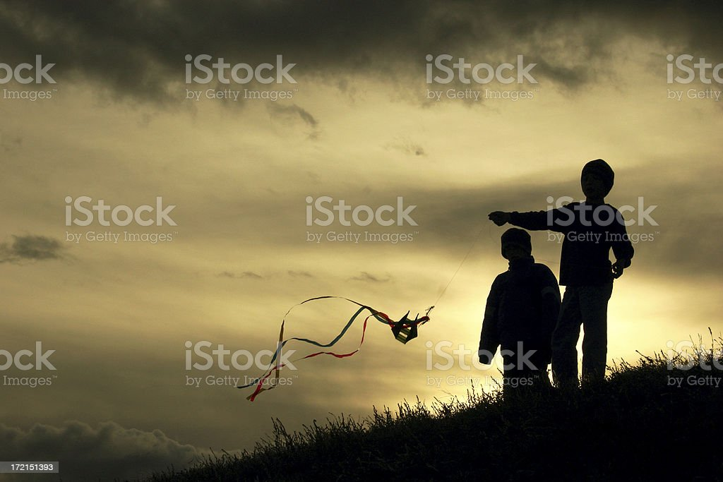 Silhouetted children flying a colorful kite at sundown stock photo