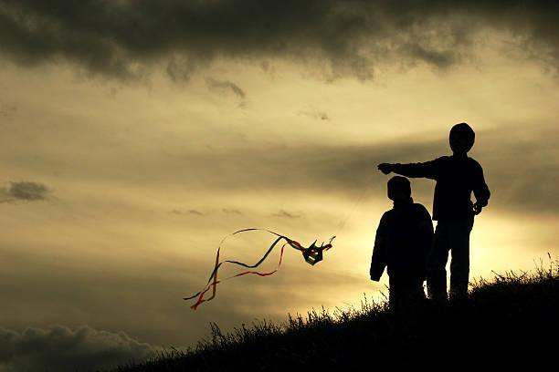 silhouetted crianças a voar um kite colorido em sundown - gradients golden ribbons imagens e fotografias de stock