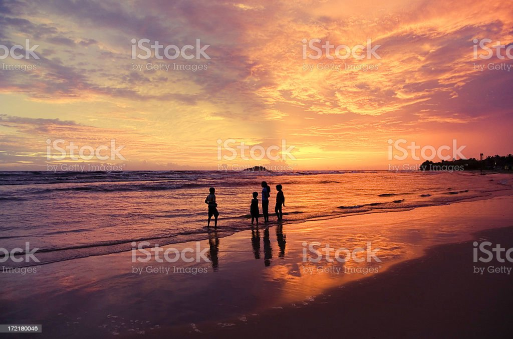 Silhouetted family on a beach at sunset royalty-free stock photo