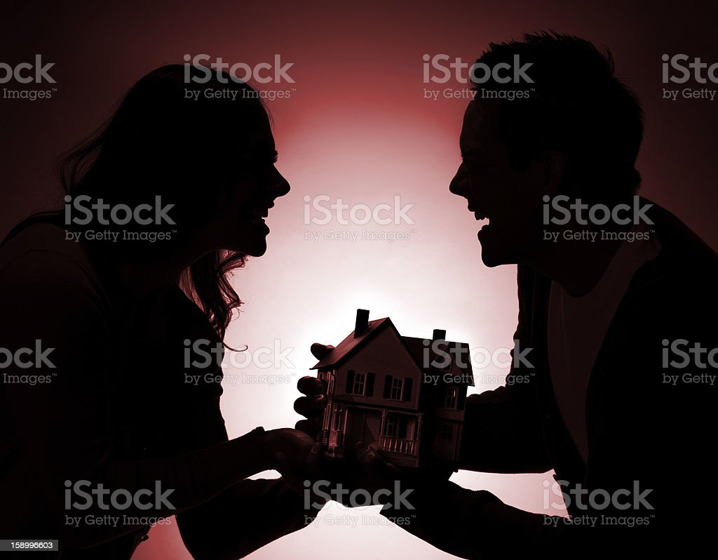 Silhouetted Fighting Couple over house stock photo