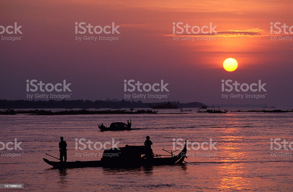 Silhouetted fishermen at sunrise on the Mekong River stock photo