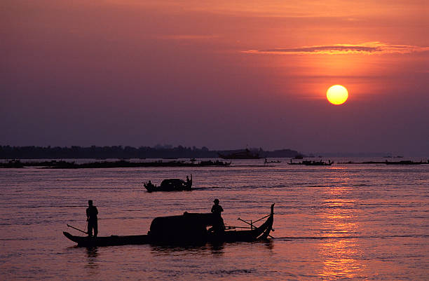 silhouetted fishermen at sunrise on the mekong river - mekong river stock pictures, royalty-free photos & images