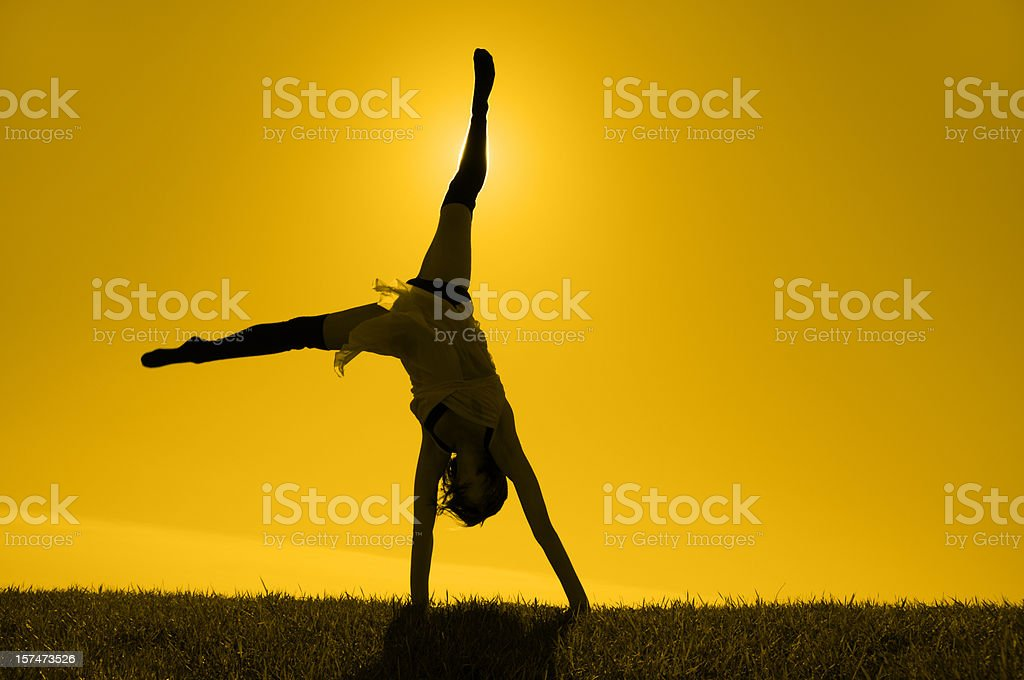 Silhouetted Girl Turning Cartwheels on Horizon In Yellow Gold Sunlight stock photo