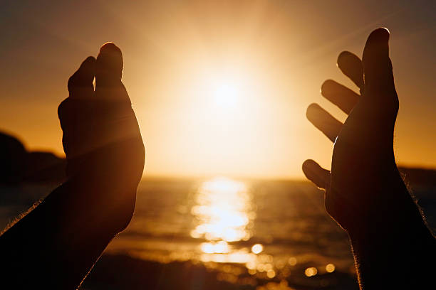 Silhouetted hands stretched out to the setting sun stock photo