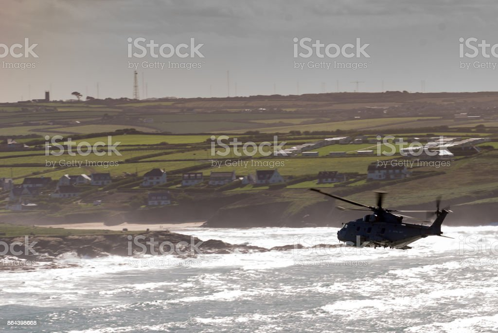 Silhouetted helicopter heads across water to a beach adn landfall stock photo