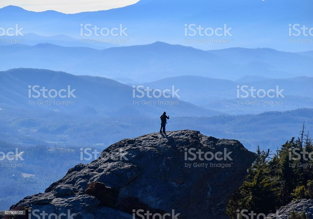 Silhouetted Man Stands Atop Grandfather Mountain Summit stock photo