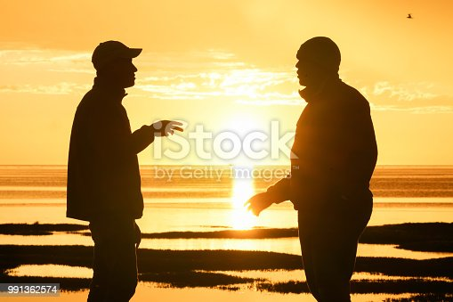 Silhouetted men back-lit by setting sun in discussion with each other.