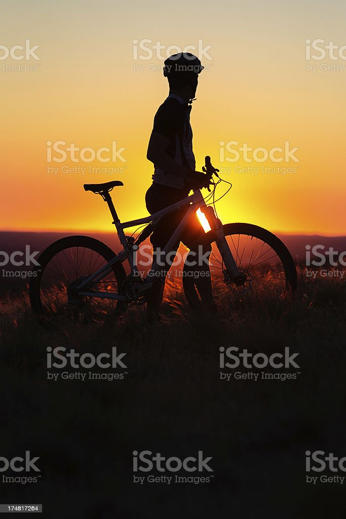 Silhouetted mountain biker watching the sunset royalty-free stock photo