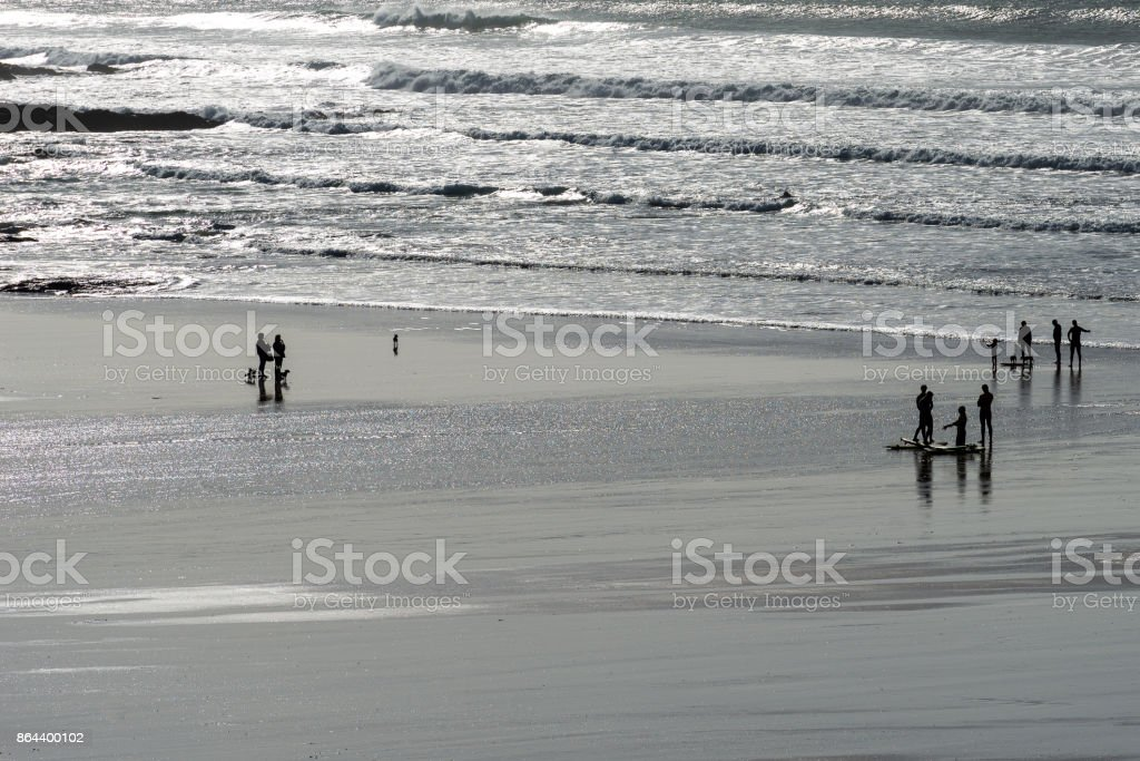 Silhouetted people on a beach stock photo