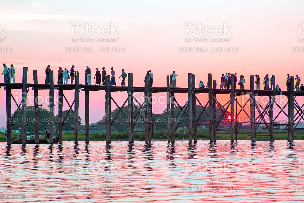 Silhouetted people on U Bein Bridge in Mandalay Myanmar stock photo
