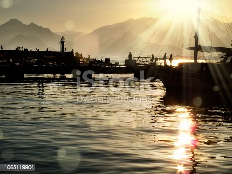 Silhouetted people relaxing in Antalya harbor over sunset sky and high mountains