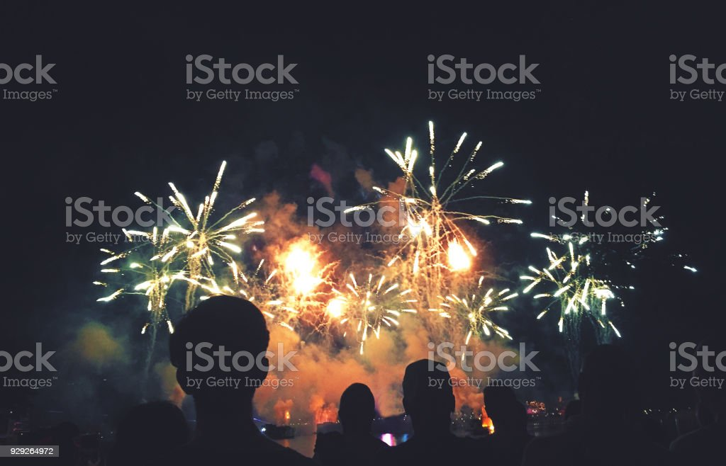 Silhouetted People Watching a Fireworks Display Crowd of Silhouetted People Watching a Colorful Fireworks Display for New Years or Fourth of July Celebration Event, Horizontal, Copy Space Back Stock Photo