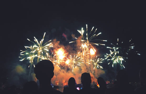silhouetted people watching a fireworks display - fireworks stock pictures, royalty-free photos & images