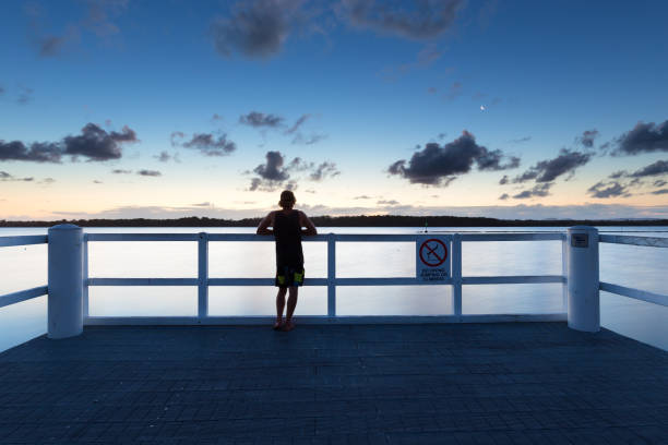 Silhouetted Person Watches the Sunset from a Pier stock photo