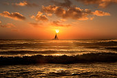 Silhouetted sailboat floating on orange color seascape view during sunset in Florida
