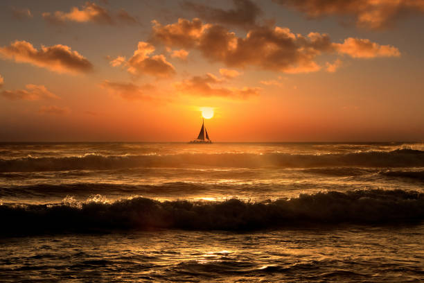 Silhouetted sailboat floating on orange color seascape over sunset sky stock photo