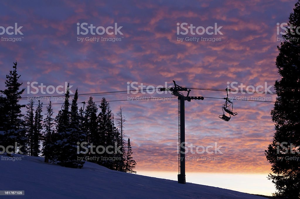 Silhouetted Ski Chair Lifts Against Pink Sunset Sky stock photo