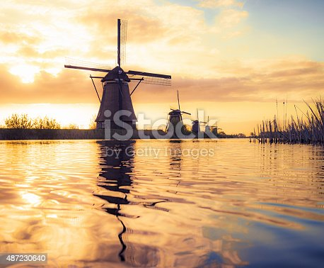 18th Century traditional Dutch windmills reflected in water at sunrise, at Kinderdijk in South Holland.