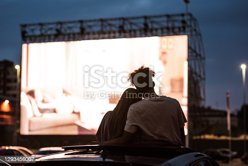 Silhouetted view of attractive young couple, boy and girl embracing, spending time together, sitting in the car while watching a movie in a drive in cinema. Entertainment, dating concept. Rear view