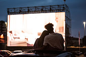 istock Silhouetted view of attractive young couple, boy and girl embracing, spending time together, sitting in the car while watching a movie in a drive in cinema 1293456007